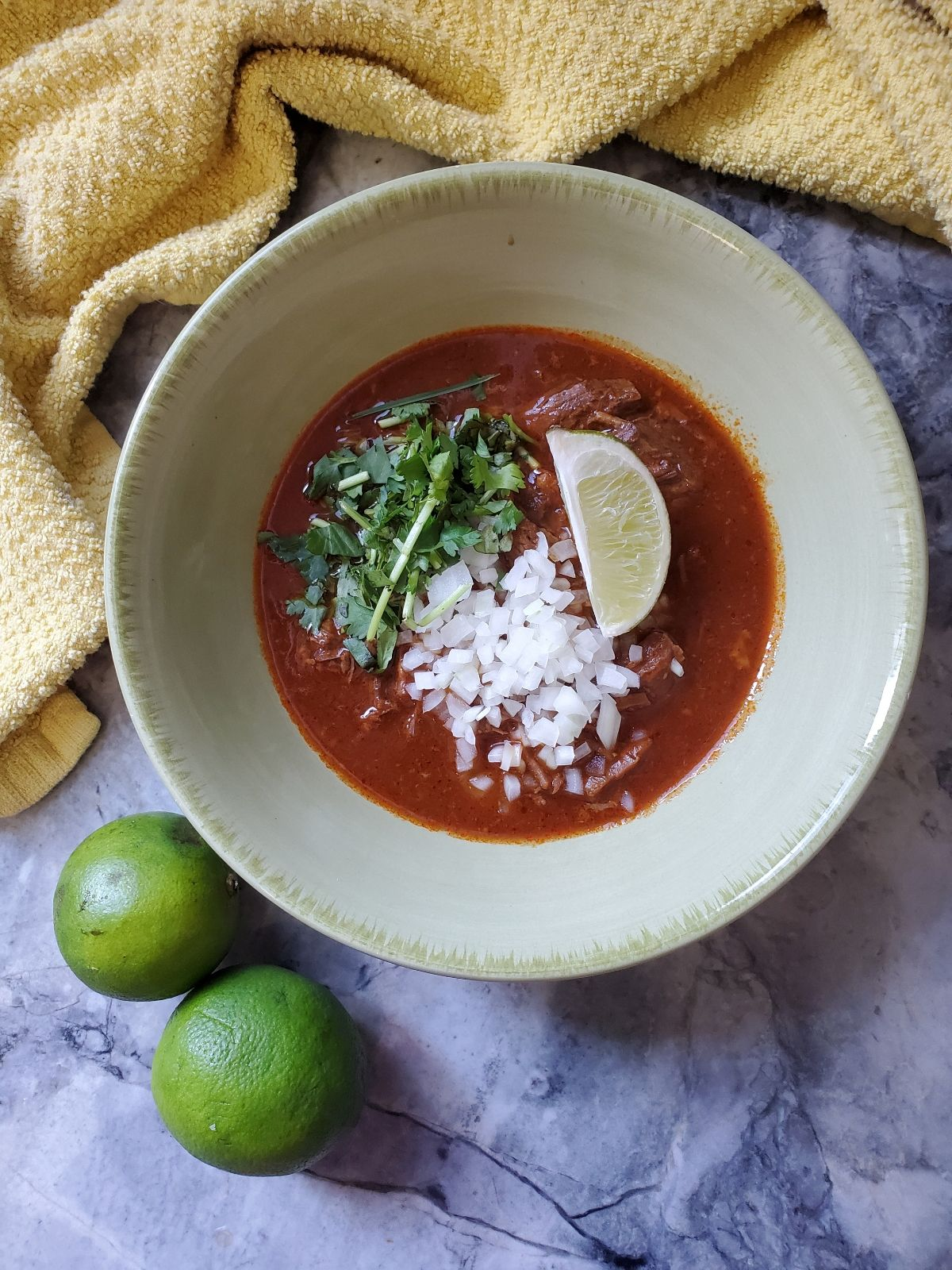 Yellow kitchen towel, a green bowl with red stew, onion, cilantro and a lime wedge, and 2 green limes in the bottom left corner