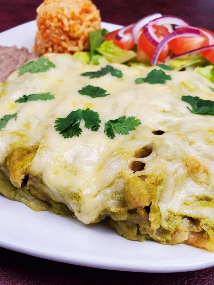green enchiladas with melted cheese on top on a white plate with beans and rice and a salad