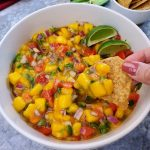 white bowl with yellow mangos, red t omatoes, and green cilantro and jalapenos