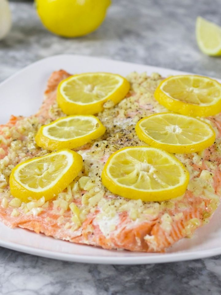 salmon with topped with garlic and lemon slices on white dish