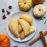 white plate with brown empanadas in the center grey back drop and 4 pumpkins around it