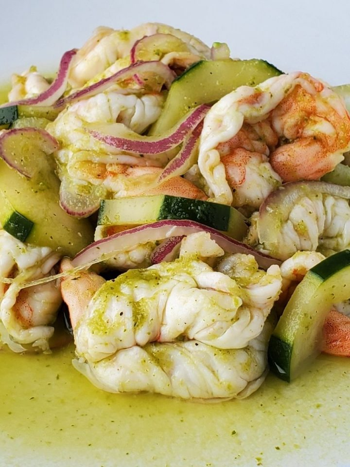 shrimp, cucumbers, and red onion slices on white place in lime juice