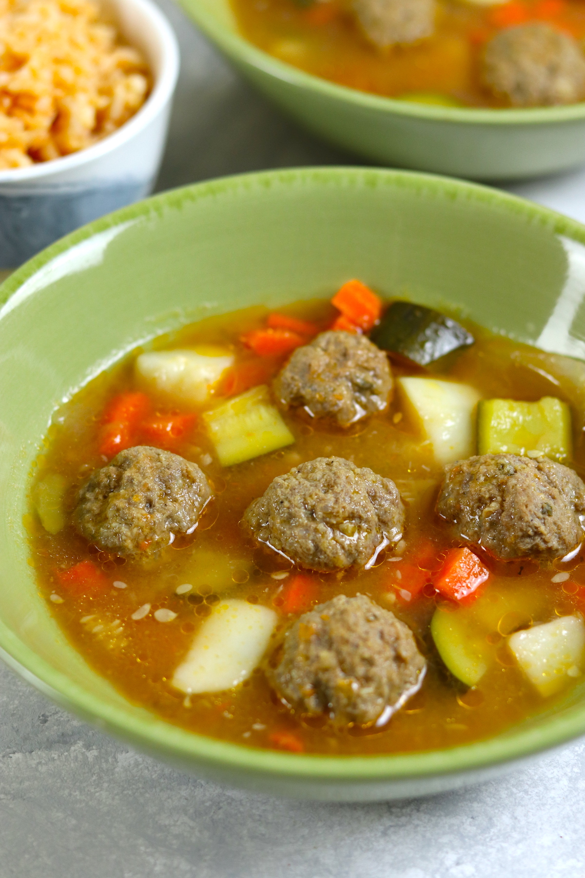 beef meatballs and vegetables in a green bowl