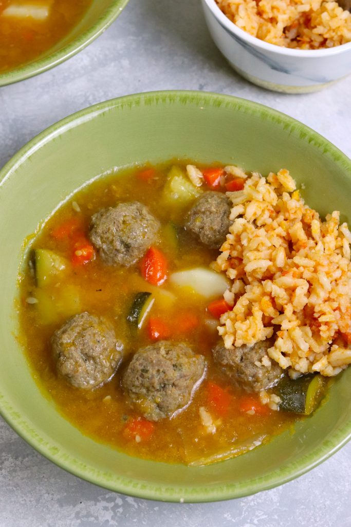 beef meatballs, rice, and vegetables in a green bowl