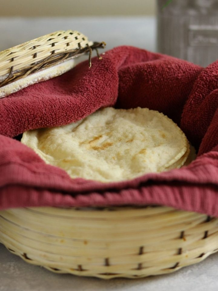 corn torillas on a red cloth inside a woven basket