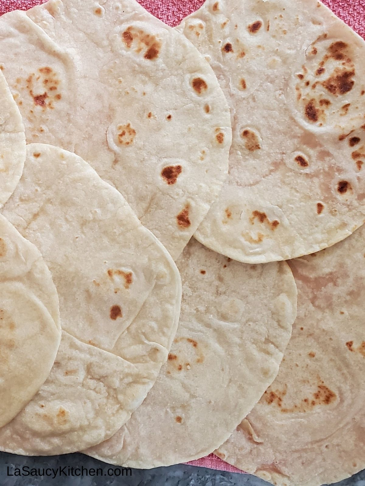 cooked flour tortillas spread out on a pink kitchen towl