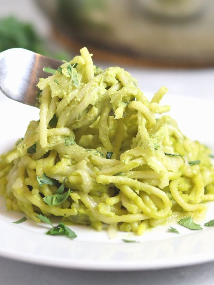 white plate with pasta in a green sauce with a for in the center in the center and cooking pan blurred in the background