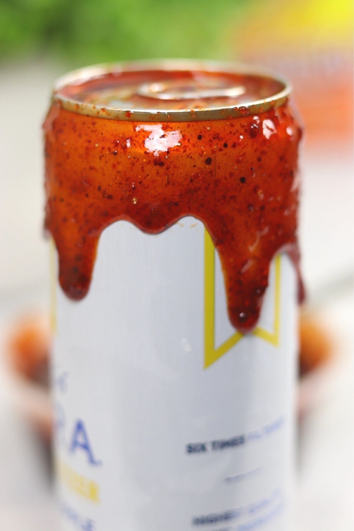 up close photo of beer can with red chamoy rimming the top as it drips down the can