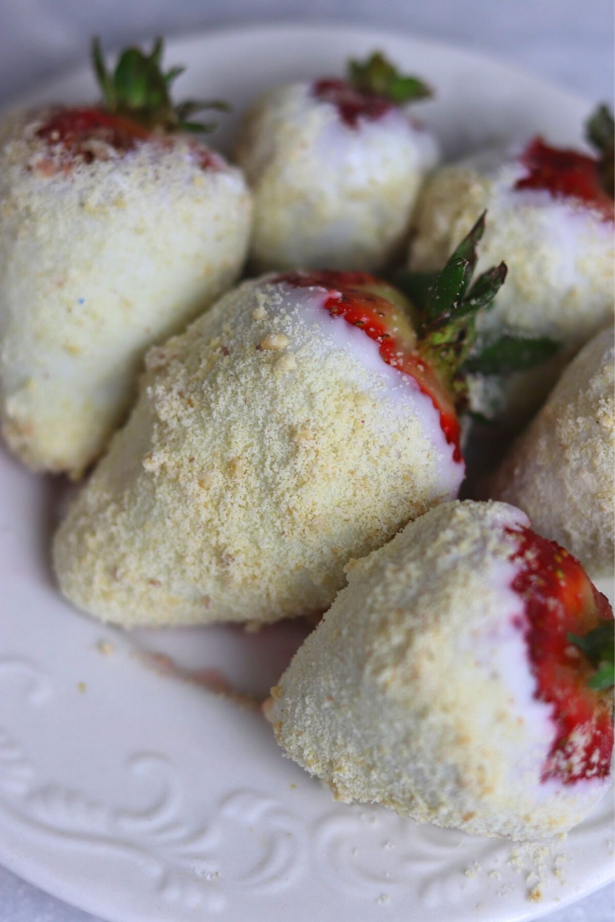 strawberries covered with peanut marzaban and white chocolate on a white plate, zoomed in on the middle strawberry.